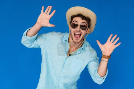 front view of excited traveler in safari hat and sunglasses standing with hands up isolated on blue