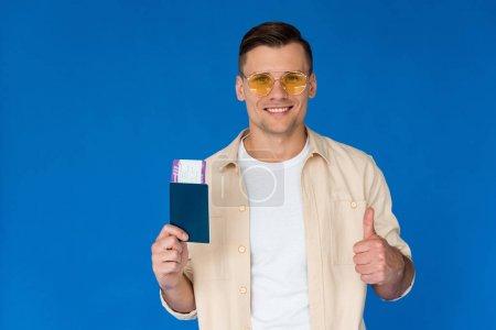 Photo pour Vue de face du touriste souriant dans des lunettes de soleil tenant passeport et montrant pouce vers le haut avec billet d'avion isolé sur bleu - image libre de droit