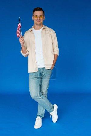 Foto de Vista de longitud completa del hombre sonriente en gafas de sol de pie con la mano en el bolsillo y la celebración de la bandera americana en azul - Imagen libre de derechos