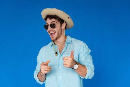 Photo pour Voyageur souriant en chapeau safari montrant pouce levé et pointant du doigt la caméra isolée sur bleu - image libre de droit
