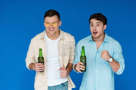Photo for Two friends holding bottles of beer and looking away isolated on blue - Royalty Free Image