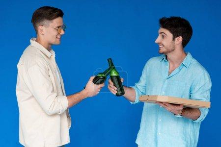 Photo pour Deux amis souriants claquant des bouteilles de bière et se regardant isolés sur bleu - image libre de droit