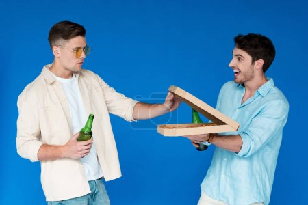 two friends holding bottles of beer and pizza isolated on blue
