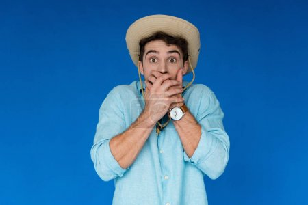 Photo for Front view of scared tourist in safari hat and wristwatch covering mouth with hands isolated on blue - Royalty Free Image