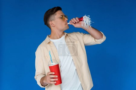 man in sunglasses holding beverage and party horn isolated on blue