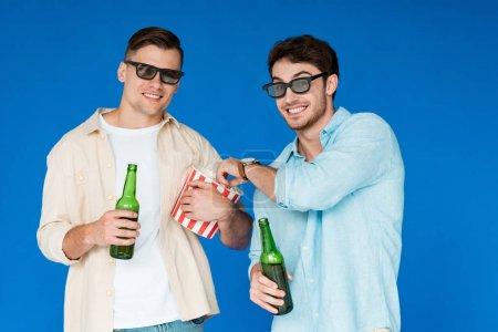 Photo pour Deux amis de sourire dans des glaces 3D retenant des bouteilles de bière et de maïs soufflé d'isolement sur le bleu - image libre de droit