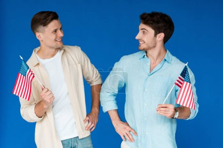 Foto de Dos amigos sonrientes sosteniendo banderas americanas y mirándose unos a otros aislados en azul - Imagen libre de derechos