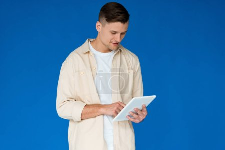 Photo for Young man in shirt using digital tablet isolated on blue - Royalty Free Image