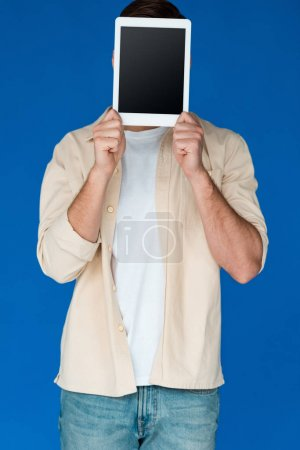 Photo for Front view of young man in shirt holding digital tablet with blank screen isolated on blue - Royalty Free Image
