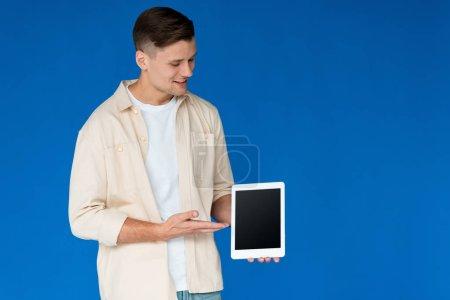 Photo pour Jeune homme souriant en chemise tenant tablette numérique avec écran blanc isolé sur bleu - image libre de droit