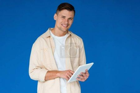 Photo pour Jeune homme souriant en chemise utilisant une tablette numérique isolée sur bleu - image libre de droit