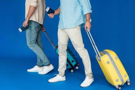Photo pour Vue recadrée de deux touristes retenant des valises et des passeports avec des billets d'avion sur le bleu - image libre de droit