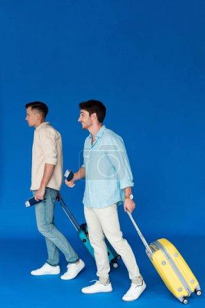 Photo pour Vue pleine longueur de deux touristes tenant des valises et des passeports avec des billets d'avion sur bleu - image libre de droit