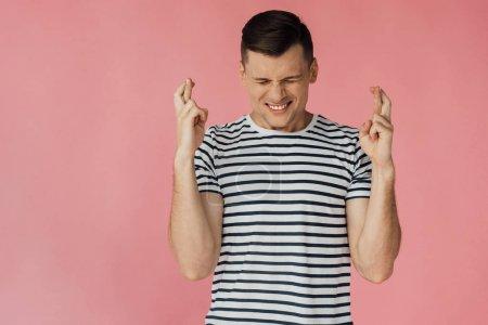 Photo pour Vue avant du jeune homme inquiété dans le t-shirt rayé avec les doigts croisés isolés sur le rose - image libre de droit