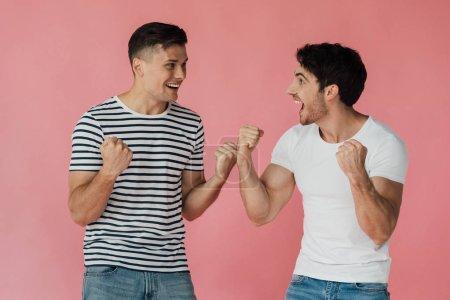 Foto de Dos amigos emocionados en camisetas mirándose el uno al otro y mostrando sí gestos aislados en rosa - Imagen libre de derechos