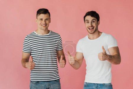 Foto de Vista frontal de dos amigos emocionados en camisetas que muestran los pulgares hacia arriba aislados en rosa - Imagen libre de derechos