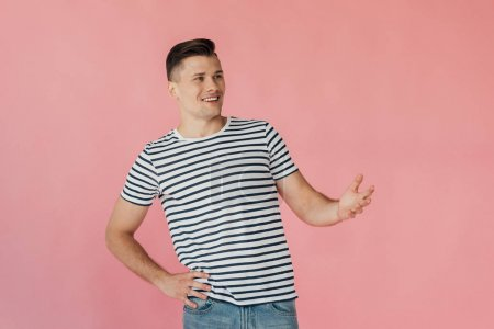 Photo for Smiling young man in striped t-shirt with hand on hip isolated on pink - Royalty Free Image