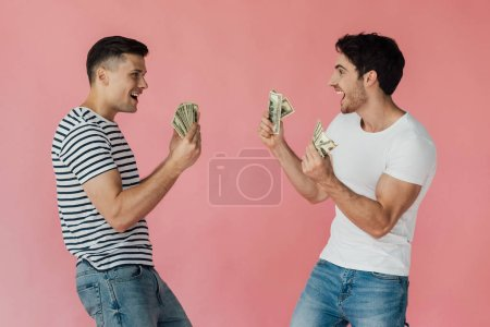 Foto de Dos amigos emocionados con billetes de dólar mirándose unos a otros aislados en rosa - Imagen libre de derechos