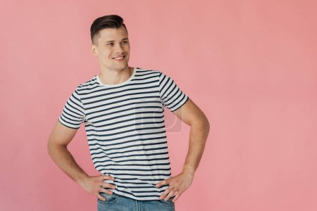Photo for Smiling young man in striped t-shirt with hands on hips isolated on pink - Royalty Free Image