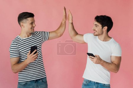 Photo for Two smiling men using smartphones and looking at each other isolated on pink - Royalty Free Image