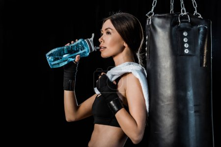 Photo for Attractive girl drinking water from sport bottle and standing near punching bag isolated on black - Royalty Free Image