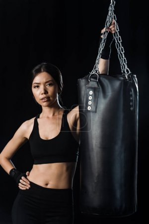 Photo for Attractive girl standing with hand in hip near punching bag isolated on black - Royalty Free Image