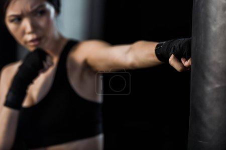 Photo pour Foyer sélectif de la femme travaillant près de sac de poinçonnage isolé sur noir - image libre de droit