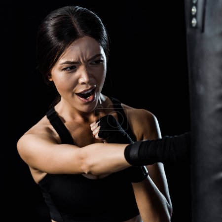 Photo for Selective focus of emotional sportswoman working out near punching bag isolated on black - Royalty Free Image