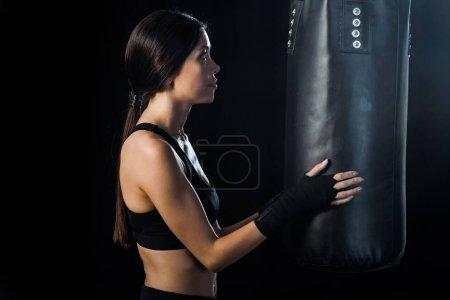 Photo pour Foyer sélectif de la sportive regardant sac de boxe isolé sur noir - image libre de droit