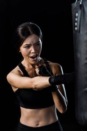 Photo pour Foyer sélectif de la boxe sportive émotionnelle près de punching bag isolé sur le noir - image libre de droit