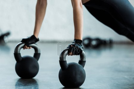 cropped view of young woman exercising with dumbbells