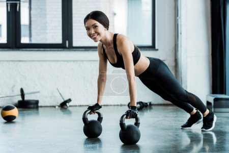 Photo for Happy woman in sportswear exercising with dumbbells - Royalty Free Image