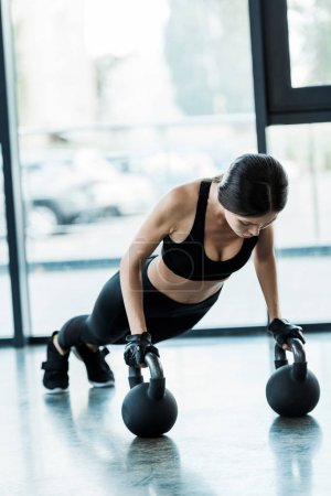 young woman in sportswear exercising with dumbbells
