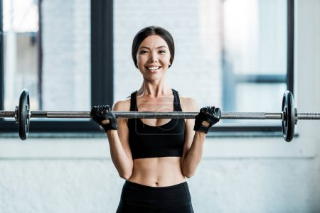 Photo for Cheerful woman working out with barbell in gym - Royalty Free Image