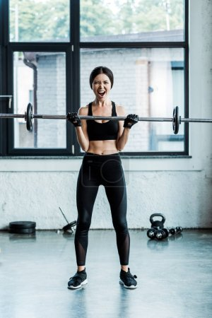 Photo for Emotional young sportswoman working out with barbell in gym - Royalty Free Image