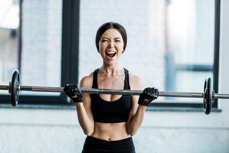 Emotionale junge Frau trainiert mit Langhantel im Fitnessstudio