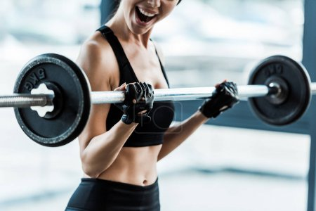 Photo for Cropped view emotional young woman working out with barbell in gym - Royalty Free Image