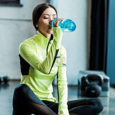 Photo for Attractive woman drinking water from sport bottle in gym - Royalty Free Image