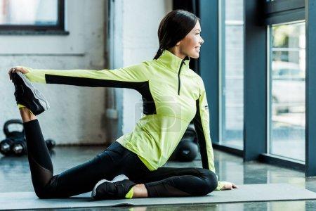 Photo pour Jeune femme heureuse s'étirant sur tapis de fitness dans la salle de gym - image libre de droit