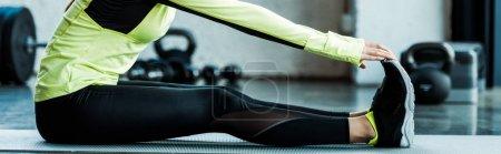 Photo pour Tir panoramique de jeune femme s'étirant sur le tapis de forme physique dans la gymnastique - image libre de droit
