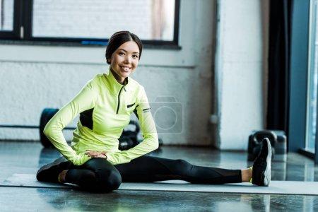 Photo pour Jeune femme gaie s'étirant sur le tapis de forme physique dans la gymnastique - image libre de droit