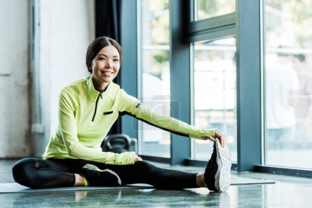 Photo for Cheerful young woman stretching on fitness mat in gym - Royalty Free Image