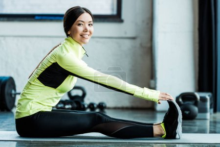 Photo for Happy young woman stretching on fitness mat in gym - Royalty Free Image