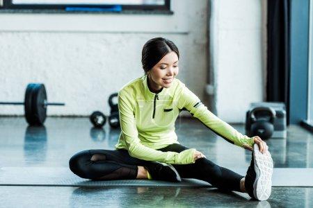 Photo pour Jeune femme heureuse dans des vêtements de sport s'étirant dans la gymnastique - image libre de droit