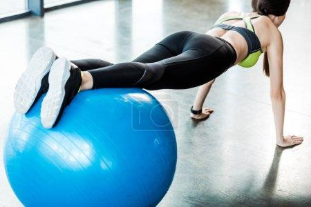 Photo pour Focus sélectif de la formation de fille sur la boule bleue de forme physique - image libre de droit