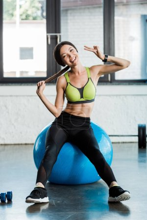 Photo for Happy girl sitting on blue fitness ball and showing peace sign in gym - Royalty Free Image