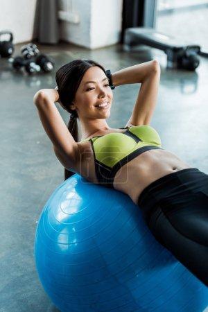 Photo pour Formation heureuse de fille sur la bille bleue de forme physique dans la gymnastique - image libre de droit