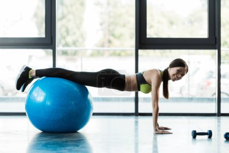 happy girl doing plank exercise on blue fitness ball in gym