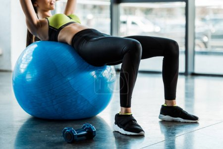 Photo for Cropped view of woman doing exercise on fitness ball - Royalty Free Image