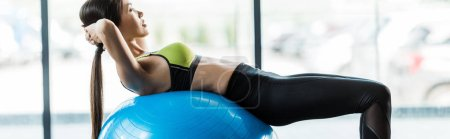 Photo pour Plan panoramique de jeune femme s'entraînant sur le ballon de fitness bleu - image libre de droit